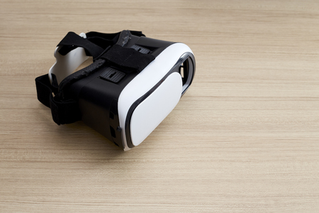 Virtual reality glasses helmet headset on wooden background. Smartphone using with virtual reality wed. Technology, simulation, hi-tech, videogame concept. Banner