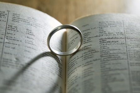 Abstract background of Silver ring old ring on a book and first love wording, Valentine concept.