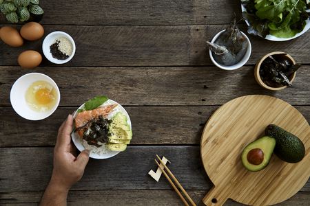 Shrimp Sashimi Rice Poke bowl with Avocado Clean and balanced healthy food concept.on dark wooden background, top view - Image Imagens - 113691332
