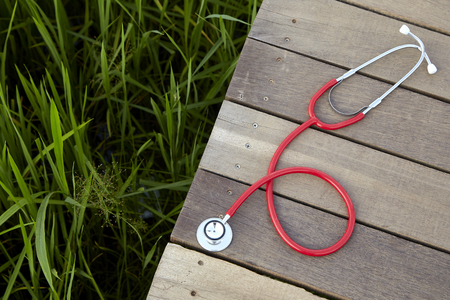 stethoscope red on wood, Concept, Doctor or medical volunteers to visit elderly people in rural Asia