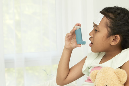 Asian girl sitting on bed and using bronco dilator inhaler for relieve asthma symptom
