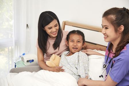 Female doctor and Young asian little patient with and mother smiling while doctor come to visit Stock Photo