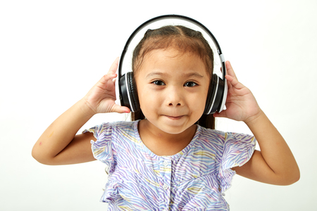 Asian Little girl in headphones listening to the music and looking to the copy space area