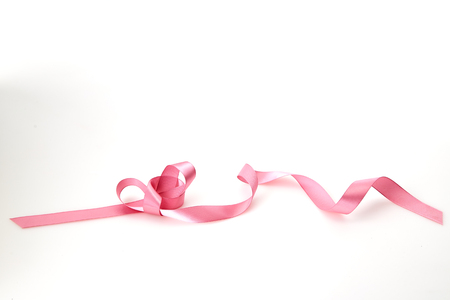 Curled pink ribbon on white background, Empty space for design