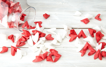 Valentines Day symbolizing love Red and white origami hearts in Glass bottle white wooden table background, Empty space for simple design