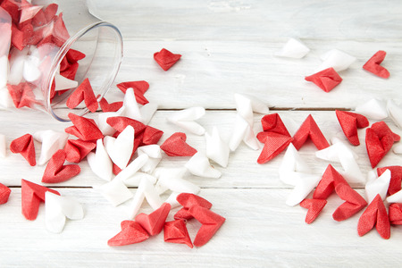 Valentine's Day symbolizing love Red and white origami hearts in Glass bottle white wooden table background, Empty space for simple design Banque d'images - 114521413