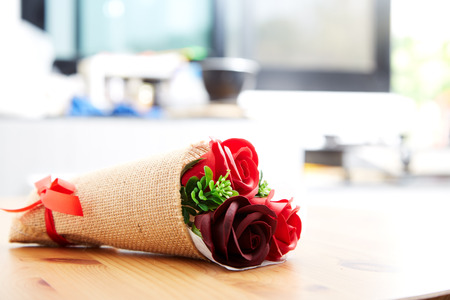 A couple gift roses on valentine day on wooden table in the kitchen, empty space for design Foto de archivo
