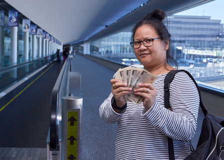 Asian Female tourists backpack standing holding money yen in the airport