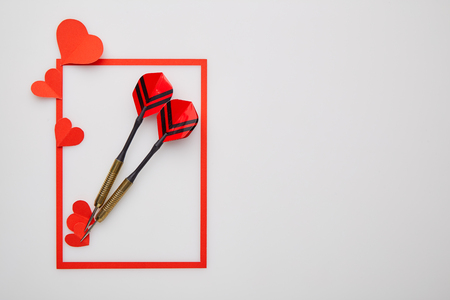 Valentine's day background with love gift, red darts and paper heart shapes. View from above. Copy space. Flat lay.