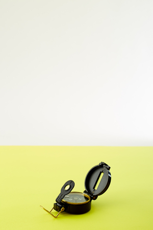 Close up Minimal Compass on bright yellow background , Concept of Travel above with copy space.