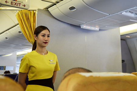 Bangkok Thailand, Jan 22 ,2019 , Airline nokscoot Interior of airplane with passengers on seats and stewardess in Yellow Flight attendant presenting a life vest on board before the flight departure