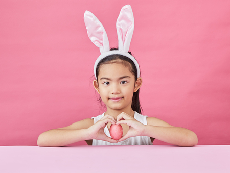 Studio shot of a happy Little girl wearing bunny ears and holding up a colorful Easter egg on a pink background Stock Photo - 126249246