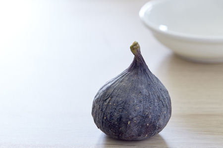 Fresh fig with plate on rustic Bright brown wooden background Imagens - 118558421