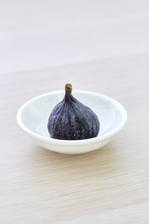 Fresh fig a plate on rustic Bright brown wooden background Imagens - 118558424