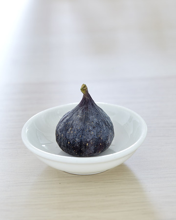 Fresh fig a plate on rustic Bright brown wooden background Imagens
