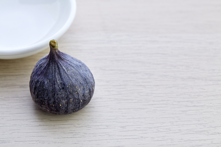 Fresh fig with plate on rustic Bright brown wooden background Imagens - 118558548