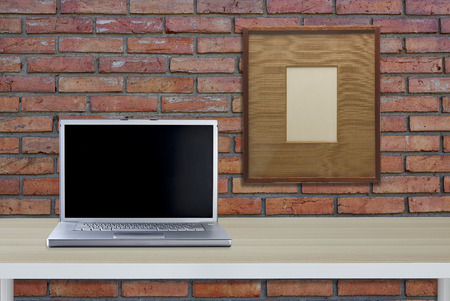 Laptop computer with black blank screen on wooden table with red brick wall background, copy space, sunlight effect, business working, online social media and searching data concept Imagens - 118558550