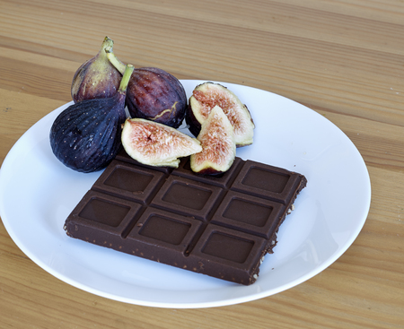Chocolate With fruit Figs a white plate onwooden background Imagens - 118558630