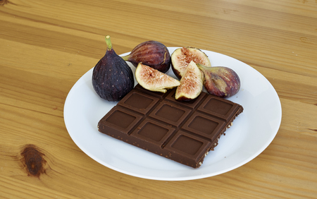 Chocolate With fruit Figs a white plate onwooden background Imagens