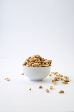 Small bowl of roasted salted peanuts on white background