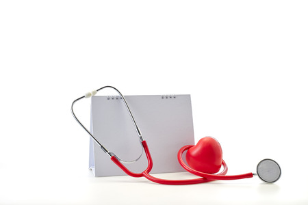 Flat 7 April Red stethoscope with empty calendar and heart shape on white background. Copy space. Healthcare. World Health Day Foto de archivo