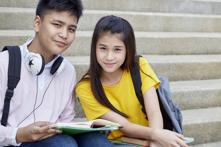 Two students guy and girl studying stairs in park of happy teen high school students outdoors
