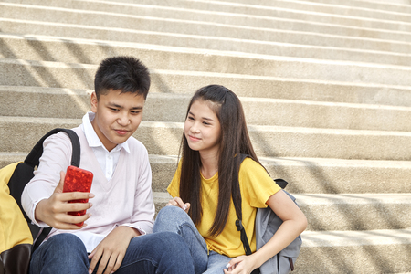 Girl and boy teens playing smiling with smartphone sitting making selfie on stair in park, friendship student,spring, summer, technology and people concept