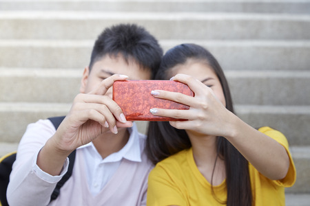 Couple asian teenager boy and girl sitting on stair and taking their photo by smartphone, Summer holiday concept