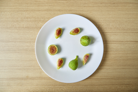 Organic Fresh green figs on white plate on a wooden background, Flat lay, Healthy fruit, top view. Space for text Archivio Fotografico
