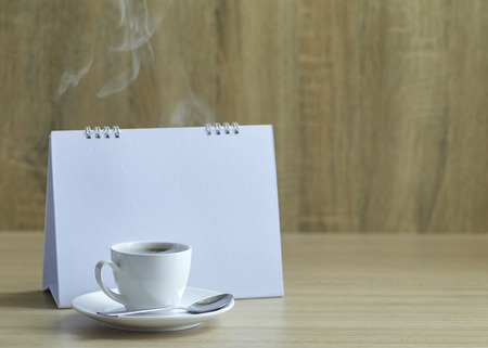 Holiday concept, Blank calendar and black coffee cup on wooden table with copy space Stok Fotoğraf