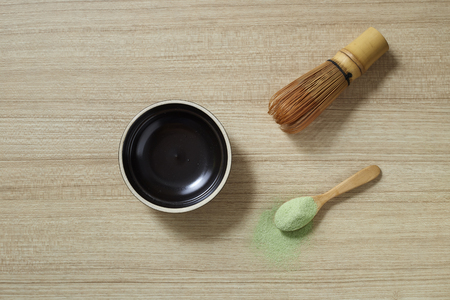 Powder organic matcha milk green tea in a spoon with bowl and bamboo whisk on wooden table, flat lay food, copy space for design Imagens - 120500210