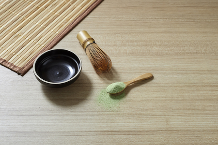 Powder organic matcha milk green tea in a spoon with bowl and bamboo whisk on wooden table, flat lay food, copy space for design Imagens - 120500239