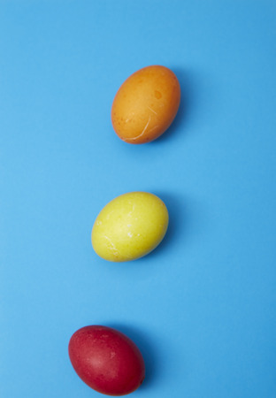 Three easter eggs red, yellow, orange on blue background. Copy space for text
