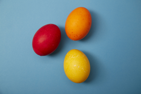 Three easter eggs red, yellow, orange on blue background. Copy space for text Imagens - 121133617