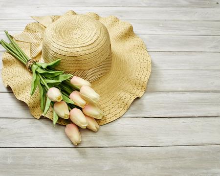 春天或夏天的郁金香和帽子在白色的木制横幅背景,母亲节,空的空间设计