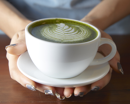 Female hands holding cup of green matcha tea on wooden