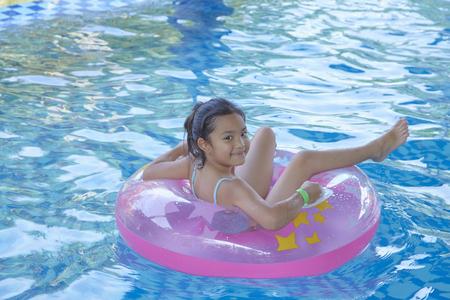 Chica asiática (9-10) sentada sobre un anillo inflable rosa en la piscina, concepto de vacaciones de verano