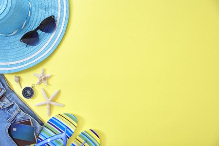 妇女的辅助部件夏天在黄色背景旅行与文本的空白。复制空间,平躺