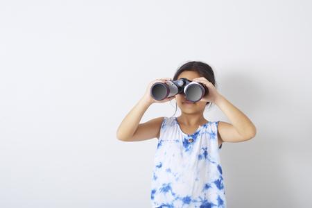 Ragazza asiatica del bambino che esamina il backgroun bianco binoculare Archivio Fotografico
