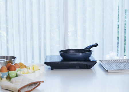 Metal black frying pan on  white Table in kitchen front of blurred curtained window background