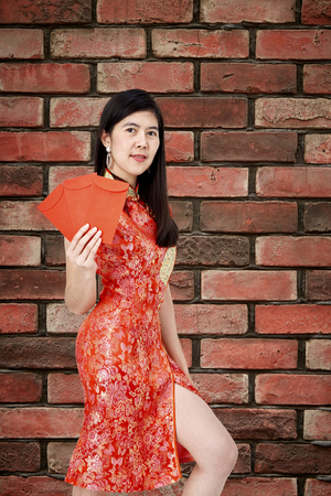 Asian pretty women in red cheongsam dress holding red envelope or ang pao on red brick wall background. is a primordial tradition of the Chinese people.