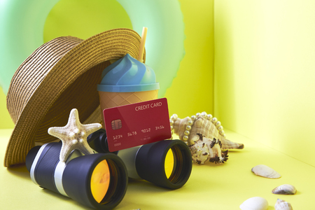 Financial travel plan concept, Composition traveler summer  vacations accessories retro binoculars ,Red Credit card and starfish  summertime on bright yellow wall background. copy space for banner 版權商用圖片