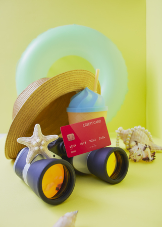 Travel plan concept, Composition traveler summer  vacations accessories retro binoculars ,Red Credit card and starfish  summertime on bright yellow wall background. copy space for banner 版權商用圖片