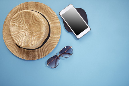 Technology, travel, summer vacation, tourism and objects concept . close up of hat, smartphone and sunglasses on bright blue background