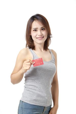 Jonge glimlachende mooie aziatische vrouw die rood creditcardvertrouwen voorstelt voor het doen van betaling Studio op witte achtergrond