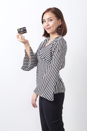 Young Asian woman holding credit card in hand, smiling to the camera, posing on white studio background