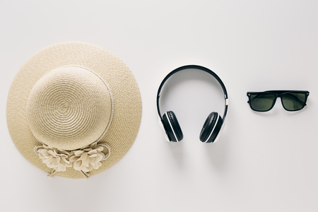 Summer holiday background, flat lay beach womens accessories: straw hat, headphones, sunglasses on white background, with empty space for text. Travel and fashion concept.