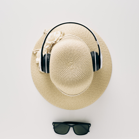 Summer holiday background, flat lay beach womens accessories: straw hat, headphones, sunglasses on white background, with empty space for text. Travel and fashion concept. Vacation summer sales.