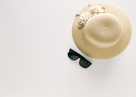 Summer holiday background, flat lay beach womens accessories: straw hat, sunglasses on white background with empty space for text. Imagens