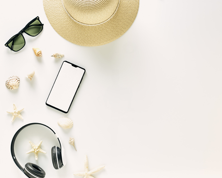 Straw hats, music headphones, sunglasses, shells on white background,  with empty space for text. Travel and fashion concept. Vacation summer sales.